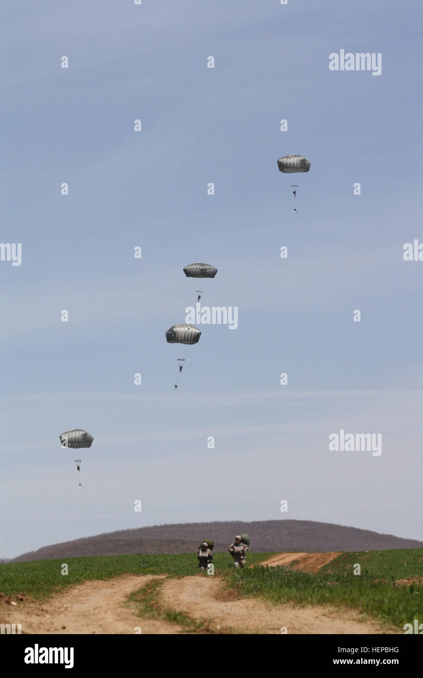 Two paratroopers assigned to Multinational Battle Group-East carry their rucksacks on their back and their parachutes Stock Photo