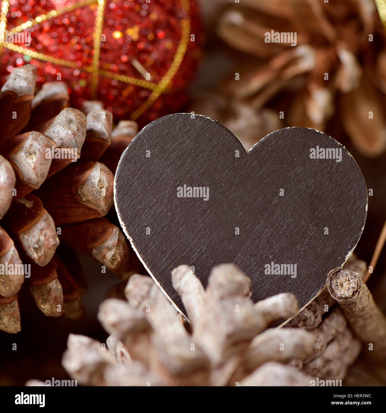 closeup of a black signboard with a blank space and a christmas ball on a pile of pine cones - Stock Image