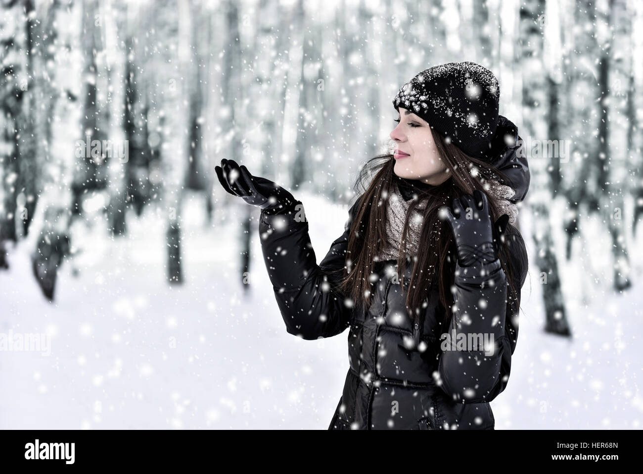 The girl with dark long hair in the winter park in snowfall - Stock Image
