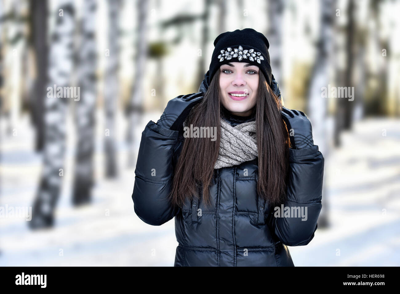 The girl with dark long hair in the winter park - Stock Image