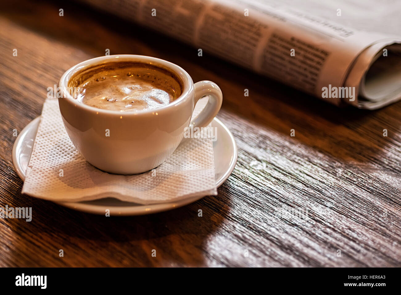 Coffee Cup and Newspaper on a Wooden Table. Good Morning or Coffee Break Concept. - Stock Image