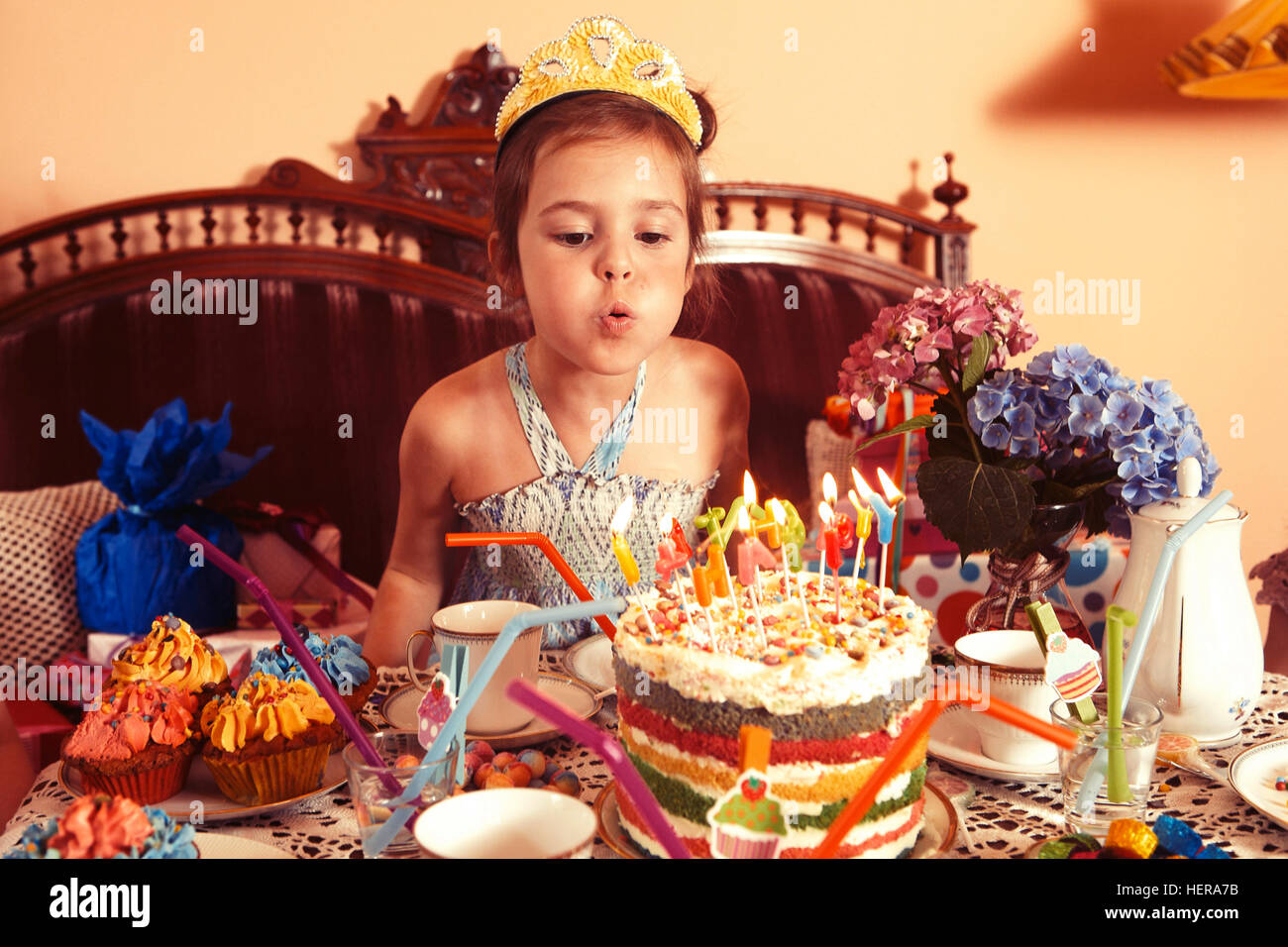 Party Girl Blows Out Candles On Her Birthday Cake Stock