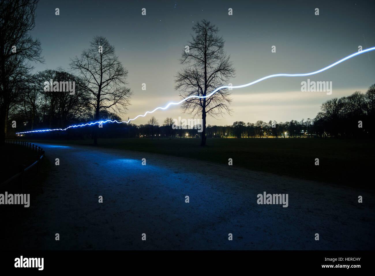 bulb exposure of a jogger with headlamp, Englischer Garten / English Garden, Munich, Bavaria, Germany - Stock Image