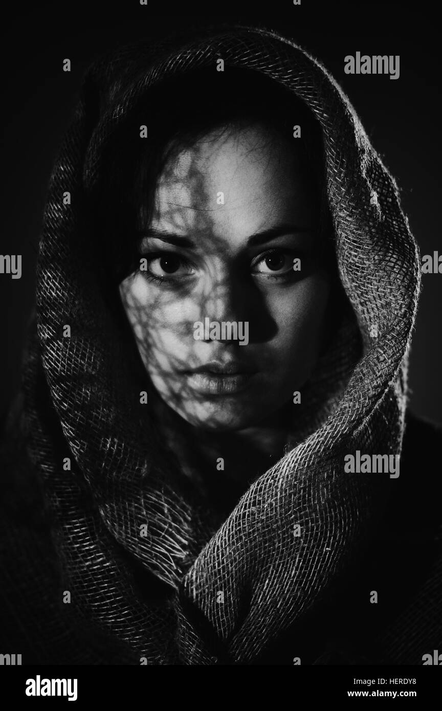 Portrait of front view beautiful woman face with a black scarf. Monochrome photo, art noise - Stock Image