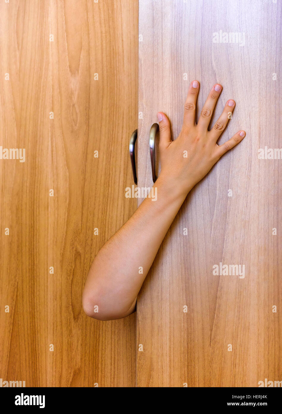 Person hand protruding from wardrobe door. Person inside of wardrobe. - Stock Image