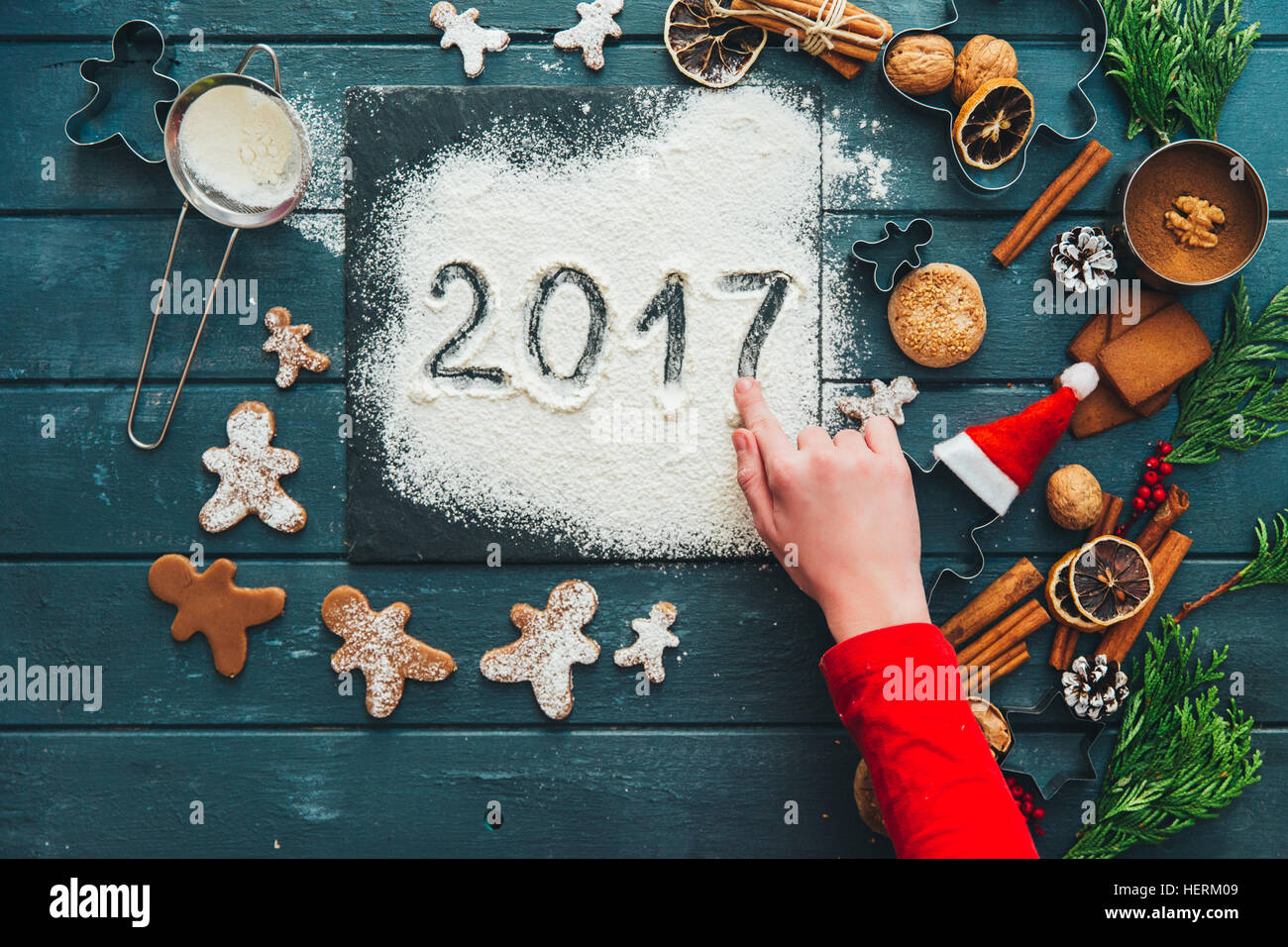 Girl making gingerbread men cookies and writing 2017 in icing sugar - Stock Image