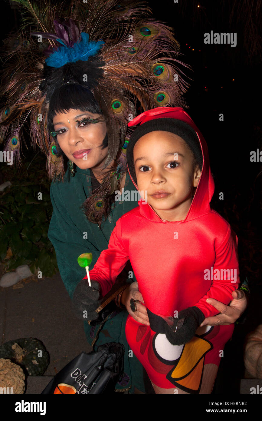 Mom wears outrageous peacock feathered hat daughter in Halloween Angry Bird costume trick or treating. St Paul Minnesota - Stock Image