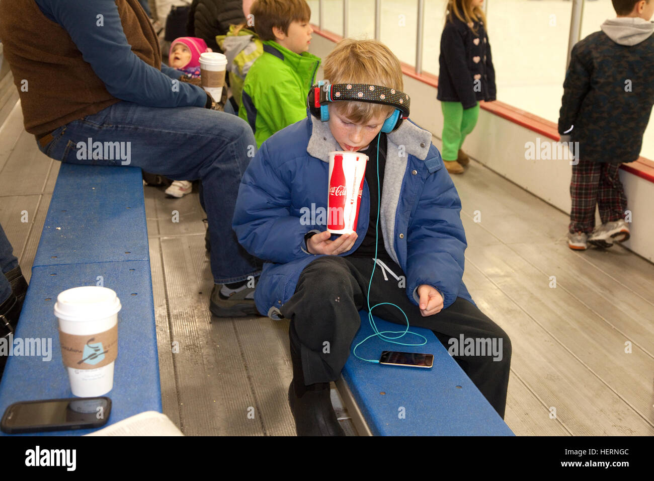 Boy age 10 sipping a large soda while listening to music from his cell phone through earphones. St Paul Minnesota - Stock Image