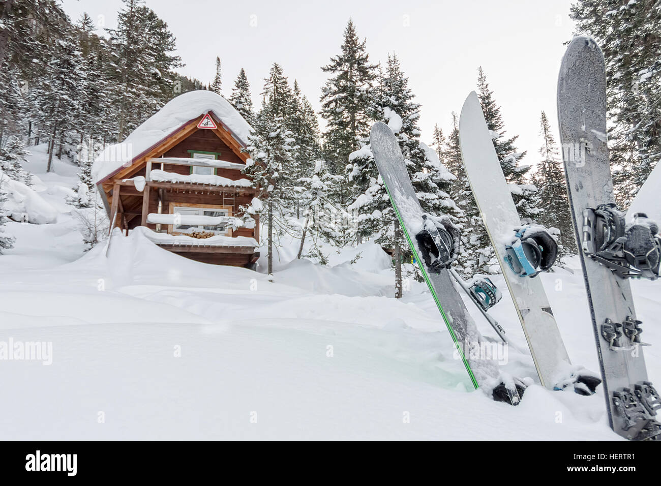 Snowboard at house chalets in winter forest with snow in mountains. - Stock Image