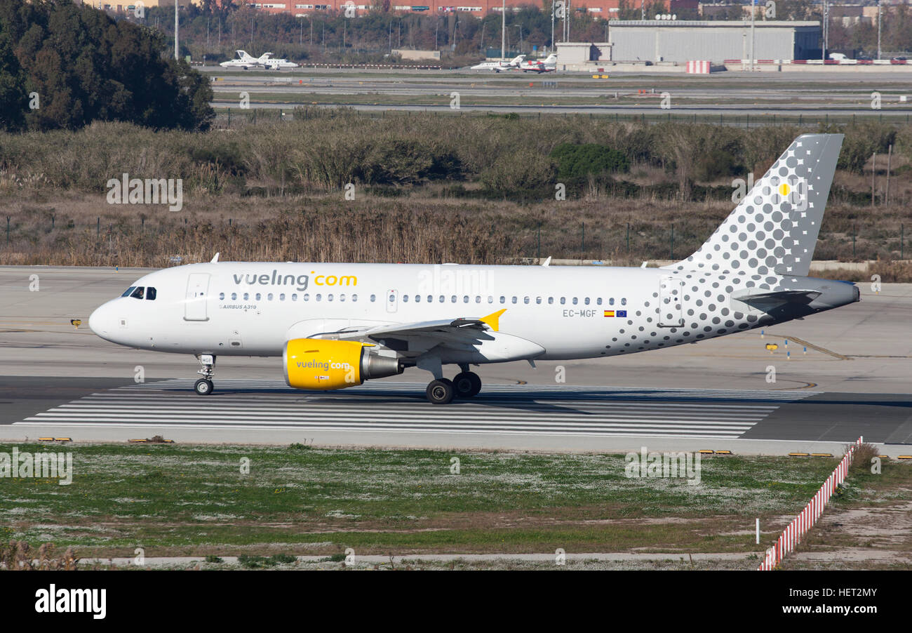 Vueling Airbus A319 taxiing along the runway at El Prat Airport in Barcelona, Spain. - Stock Image