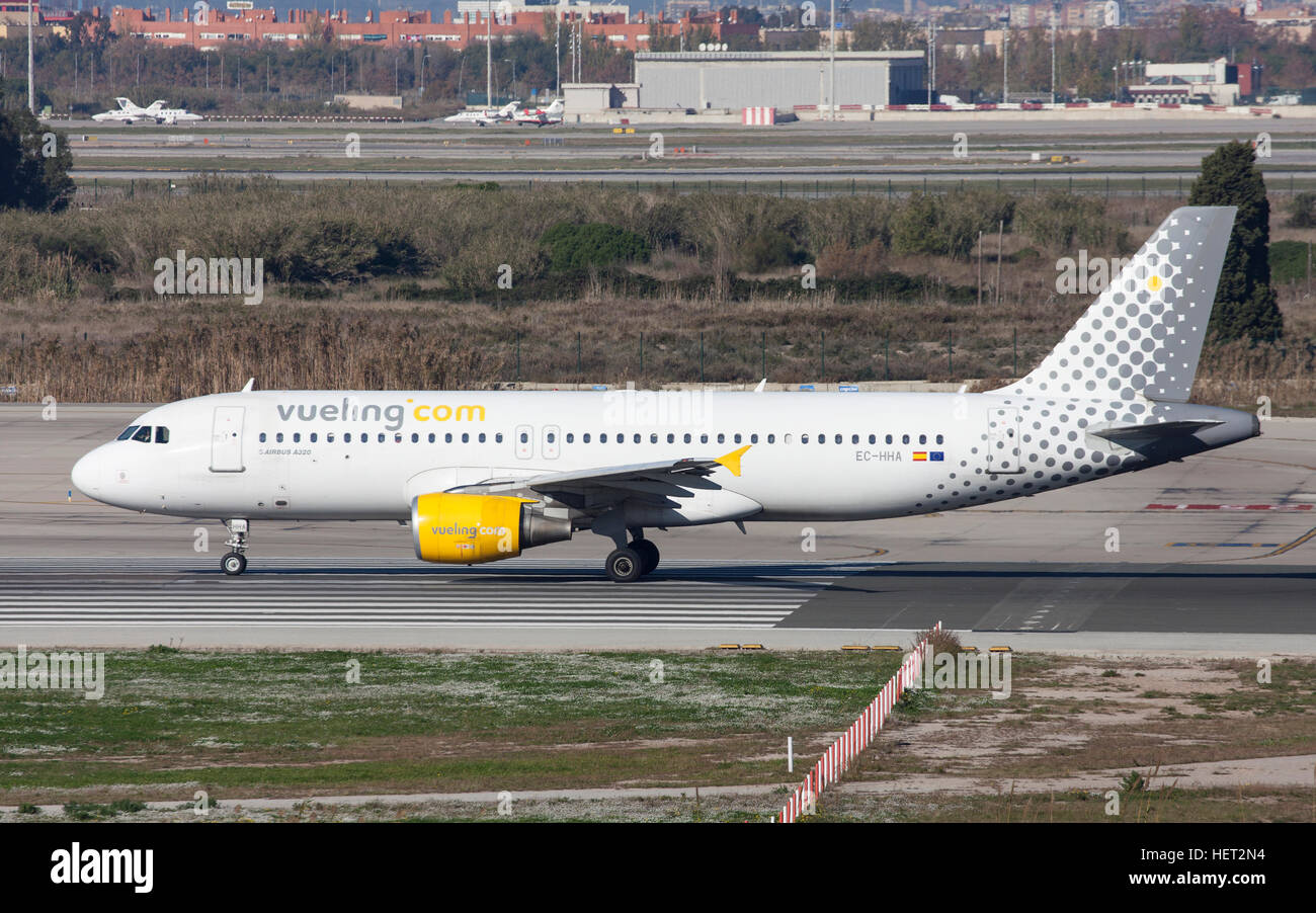Vueling Airbus A320 taxiing along the runway at El Prat Airport in Barcelona, Spain. - Stock Image