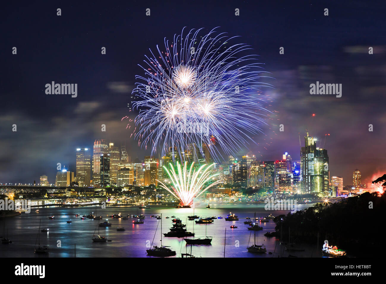 Sydney city CBD at New Year eve Fireworks over still water of Harbour. Blue light ball illuminate towers and landmarks Stock Photo