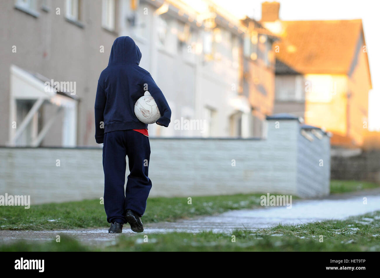 A boy walks on a snow covered path on the Gurnos Counci housingl estate in Merthyr Tydfil, South Wales, UK. Stock Photo