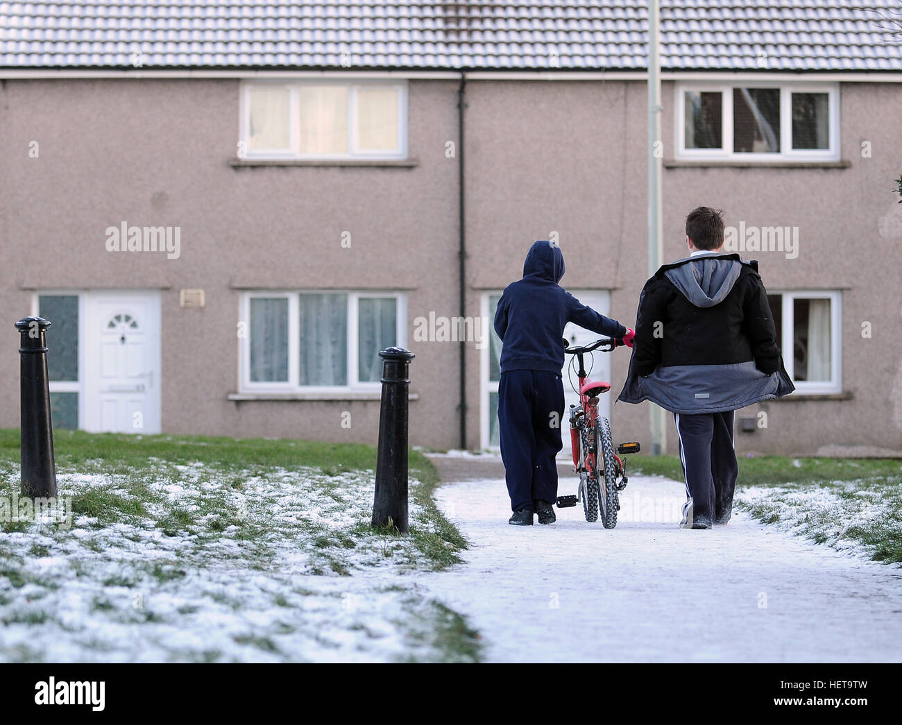 Two young boys walk on a snow covered path on the Gurnos housing Council estate in Merthyr Tydfil, South Wales, Stock Photo