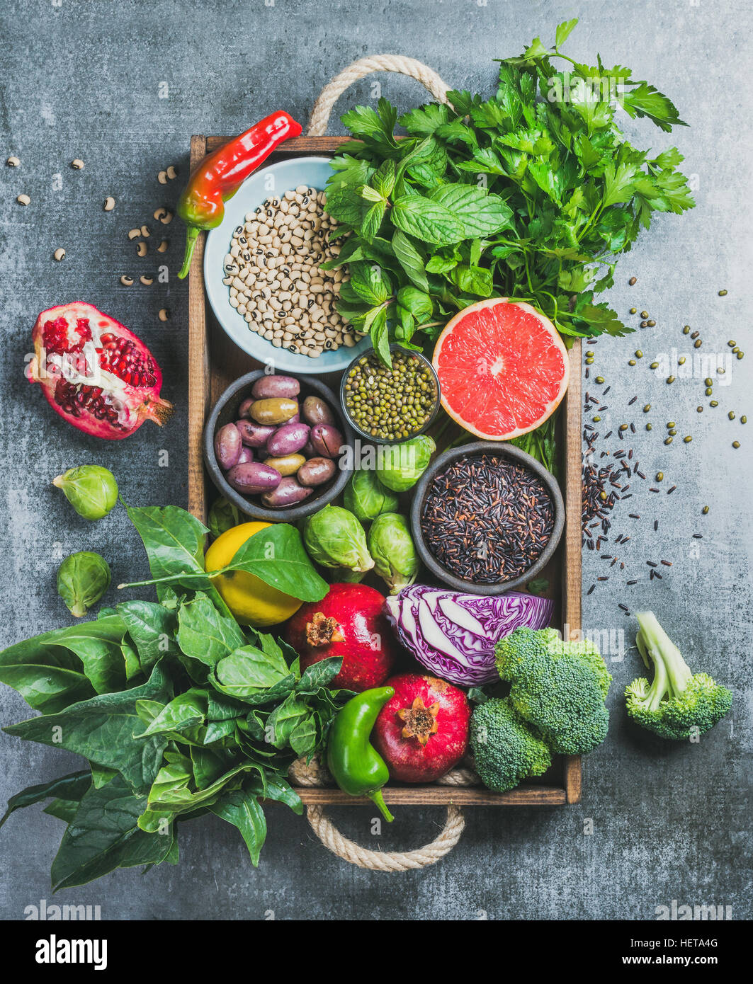 Healthy food ingredients in wooden box over grey background - Stock Image