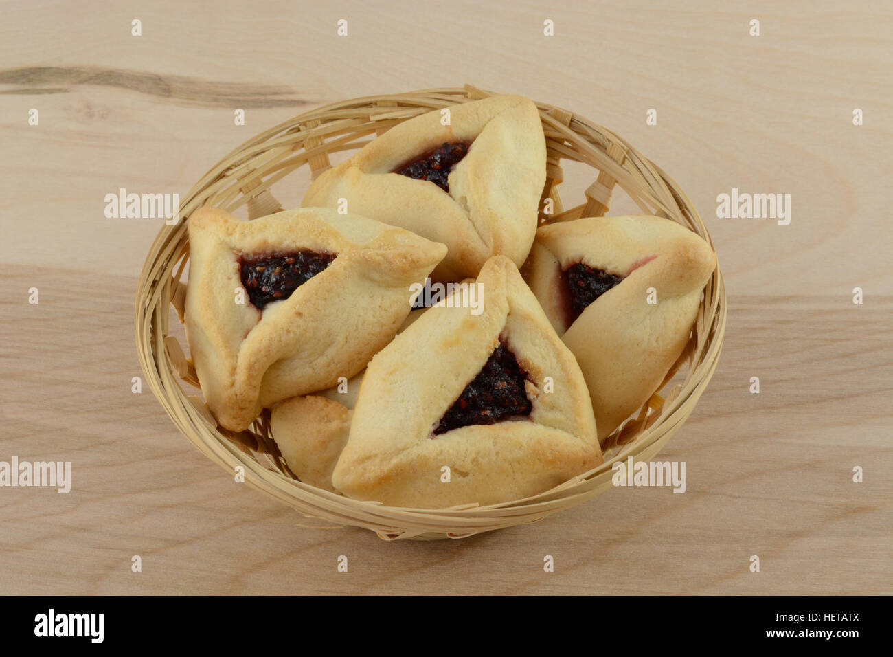 Hamantaschen raspberry pastries in wicker basket on table - Stock Image