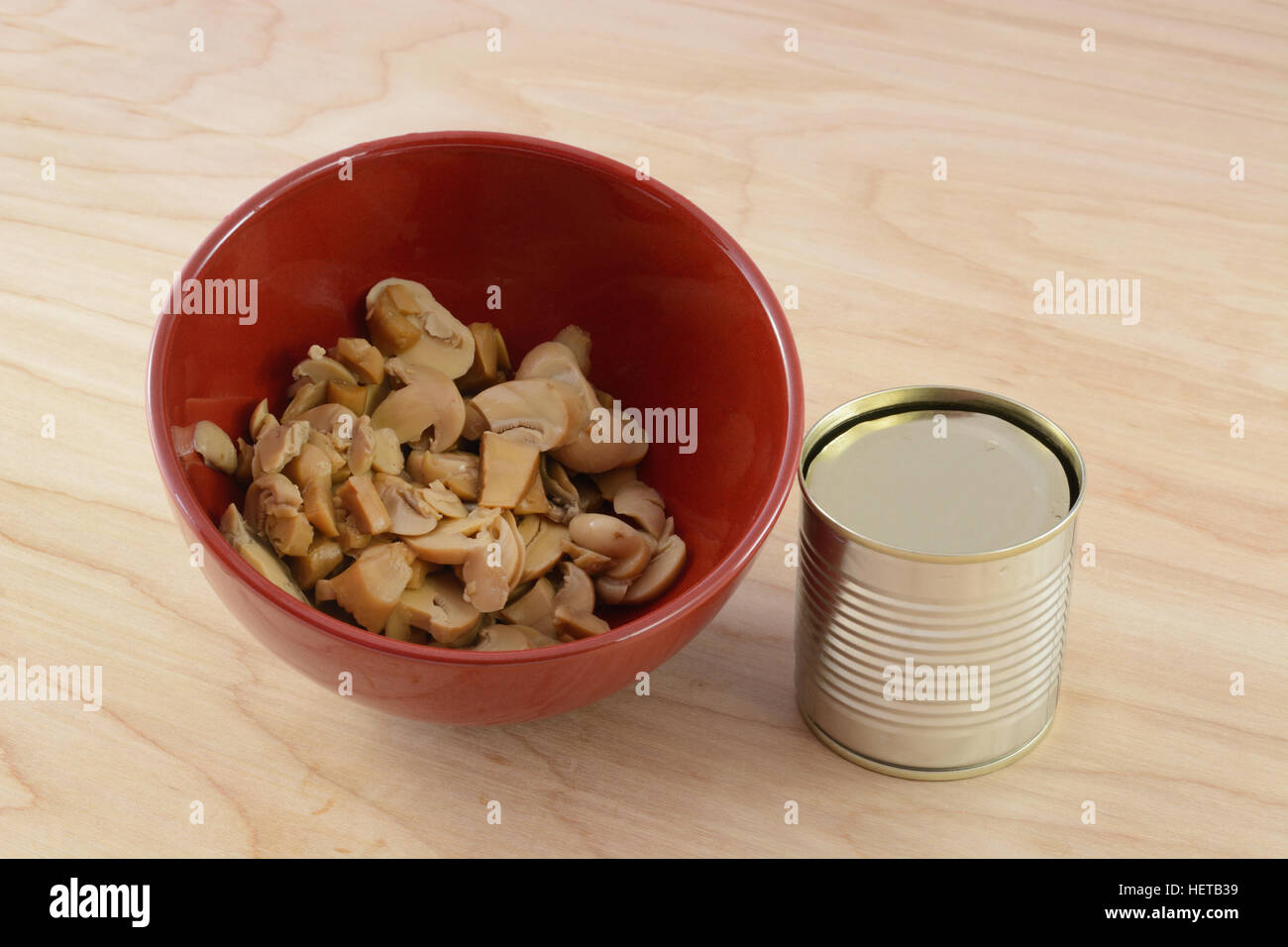 Canned mushrooms in red bowl with can on wooden kitchen table - Stock Image