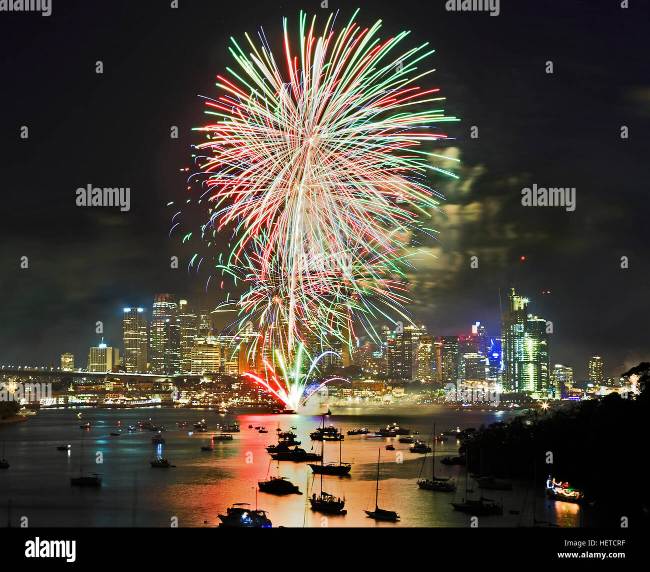 Sydney New Year Fireworks over city CBD and harbour waters with crowd of specators and yachts. Multi-colour light - Stock Image