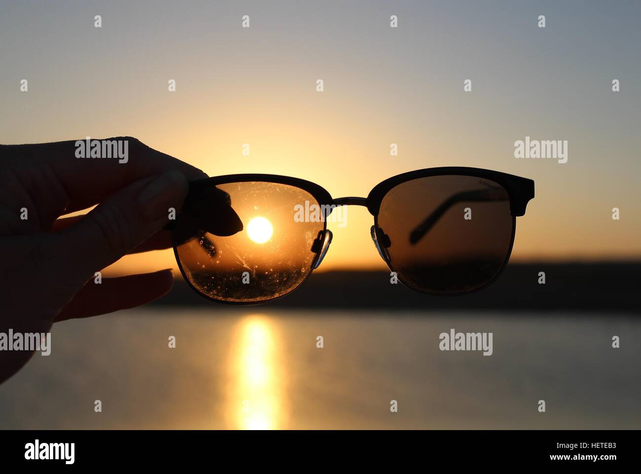 the sunsetting and the sun shinning through an sunglass lense also the sun reflecting on the water - Stock Image