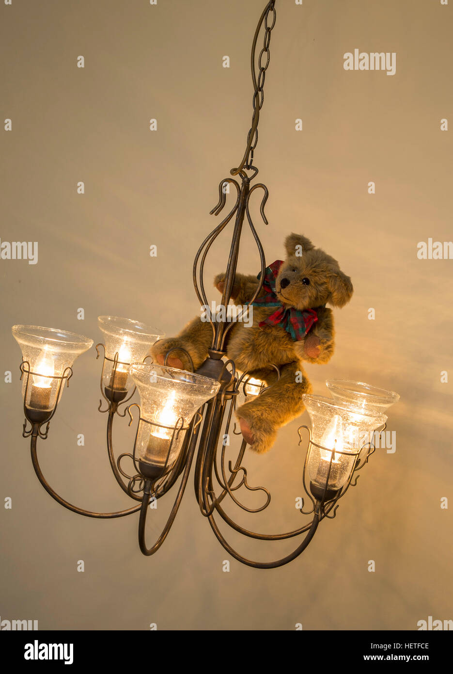 Teddy bear wearing a christmas bow swinging from a chandelier stock teddy bear wearing a christmas bow swinging from a chandelier aloadofball Image collections