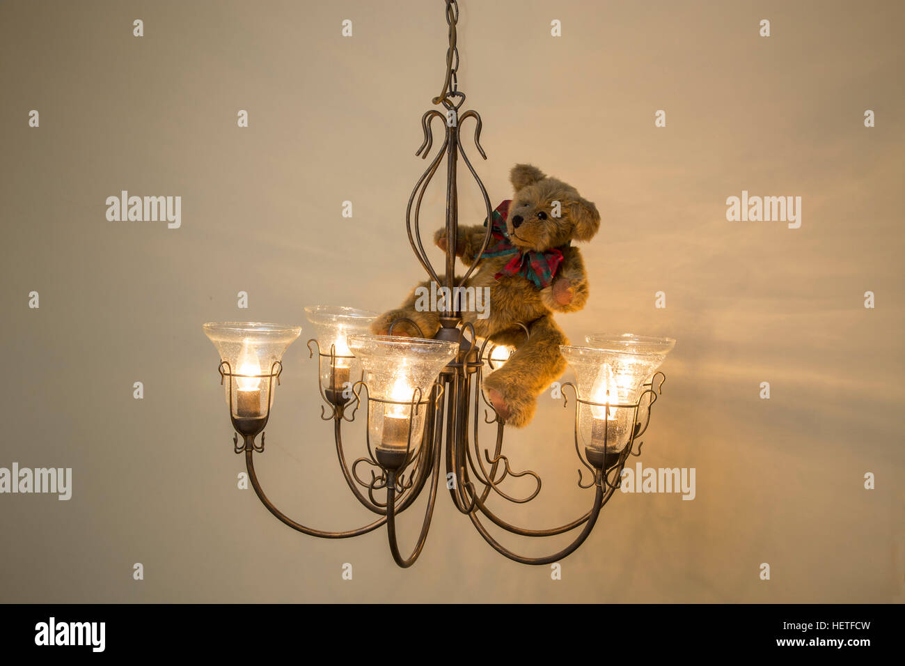 Teddy bear wearing a christmas bow swinging from a chandelier stock teddy bear wearing a christmas bow swinging from a chandelier arubaitofo Choice Image