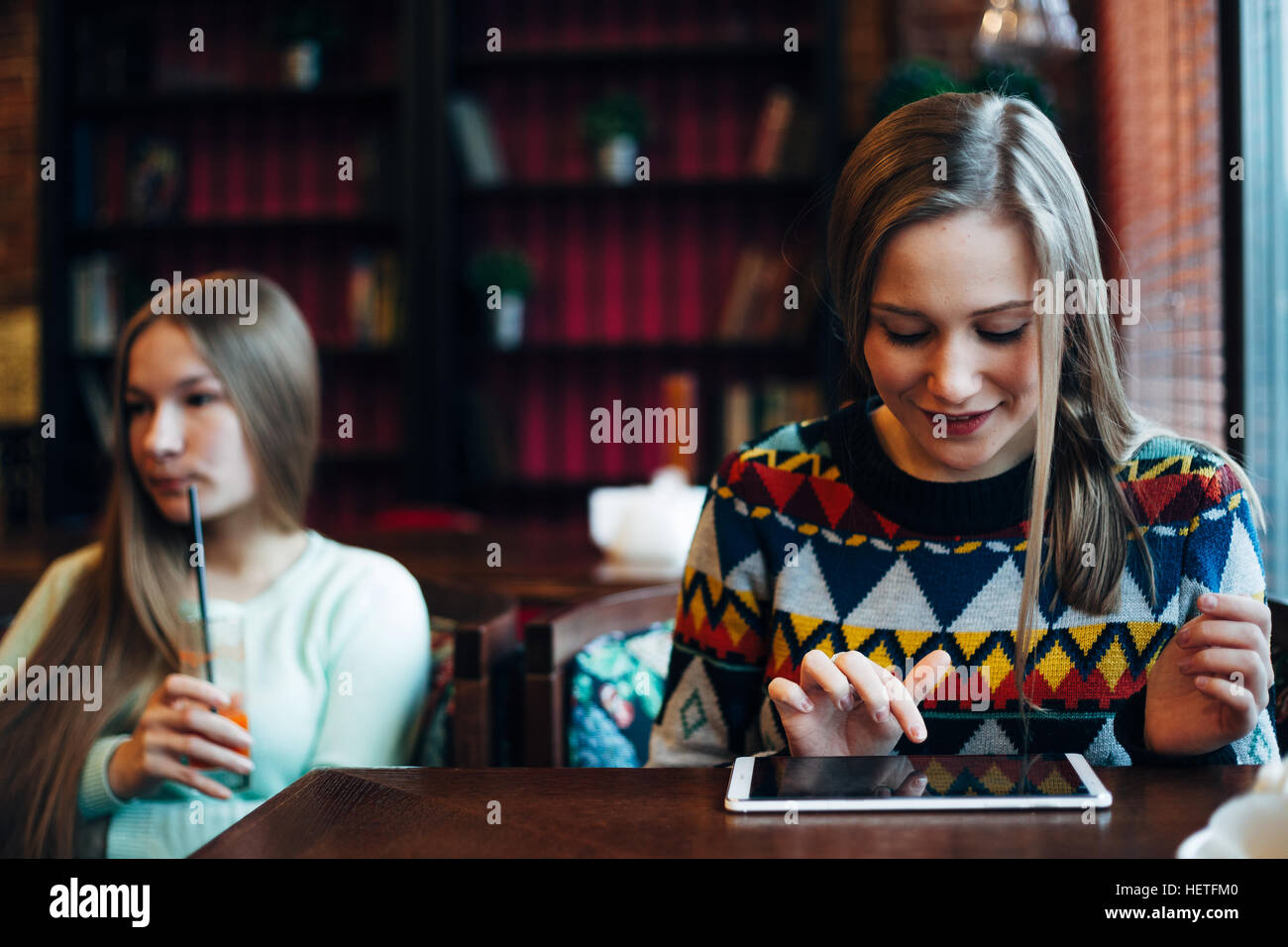 Girl friends communicate in a cafe - Stock Image