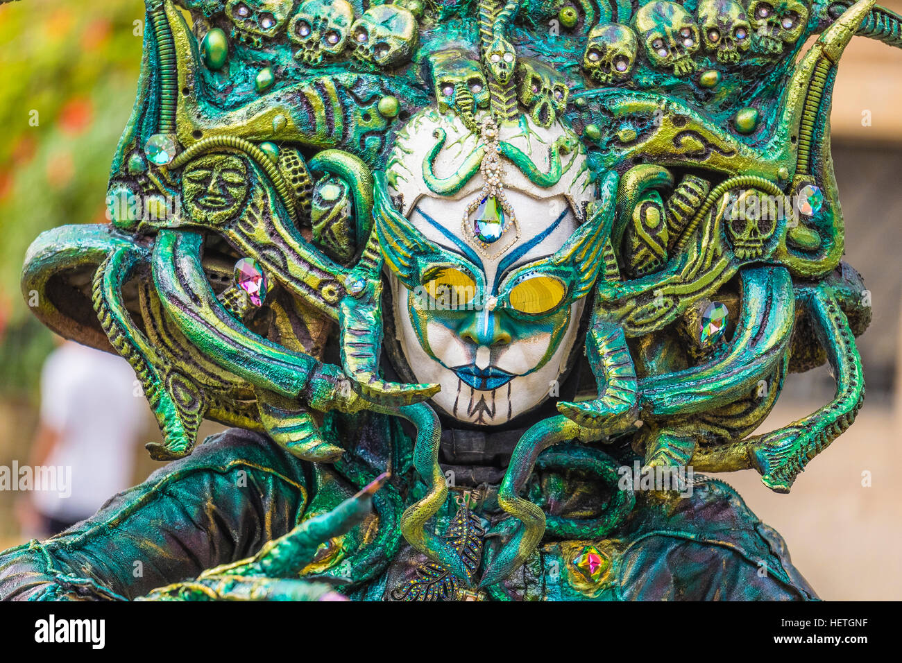 Head and shoulders of street performer in weird green headdress costume, with skulls, snakes and gold colored glasses/eyes. - Stock Image