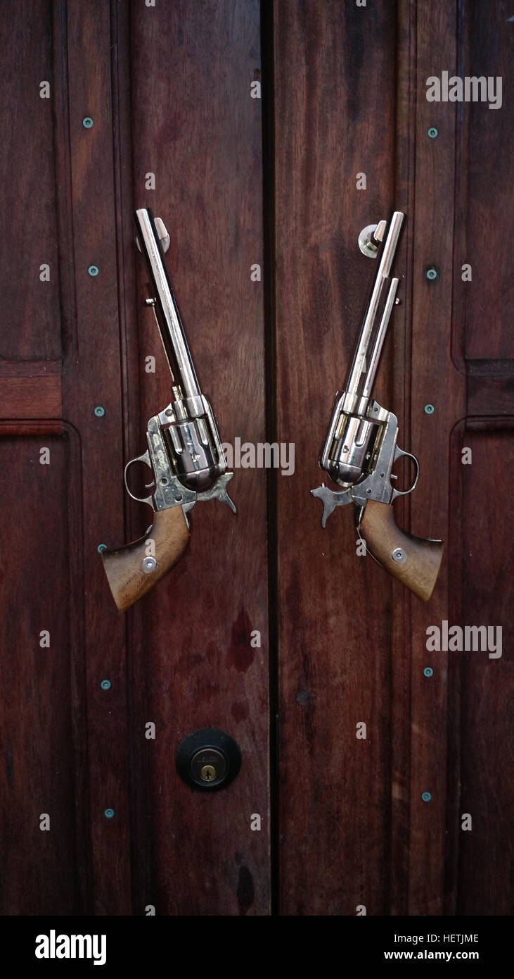 Pistols Serve As Door Pulls On A Rustic Door In Washington. The Guns Are  The Type Once Used By Cowboys In The Old West.