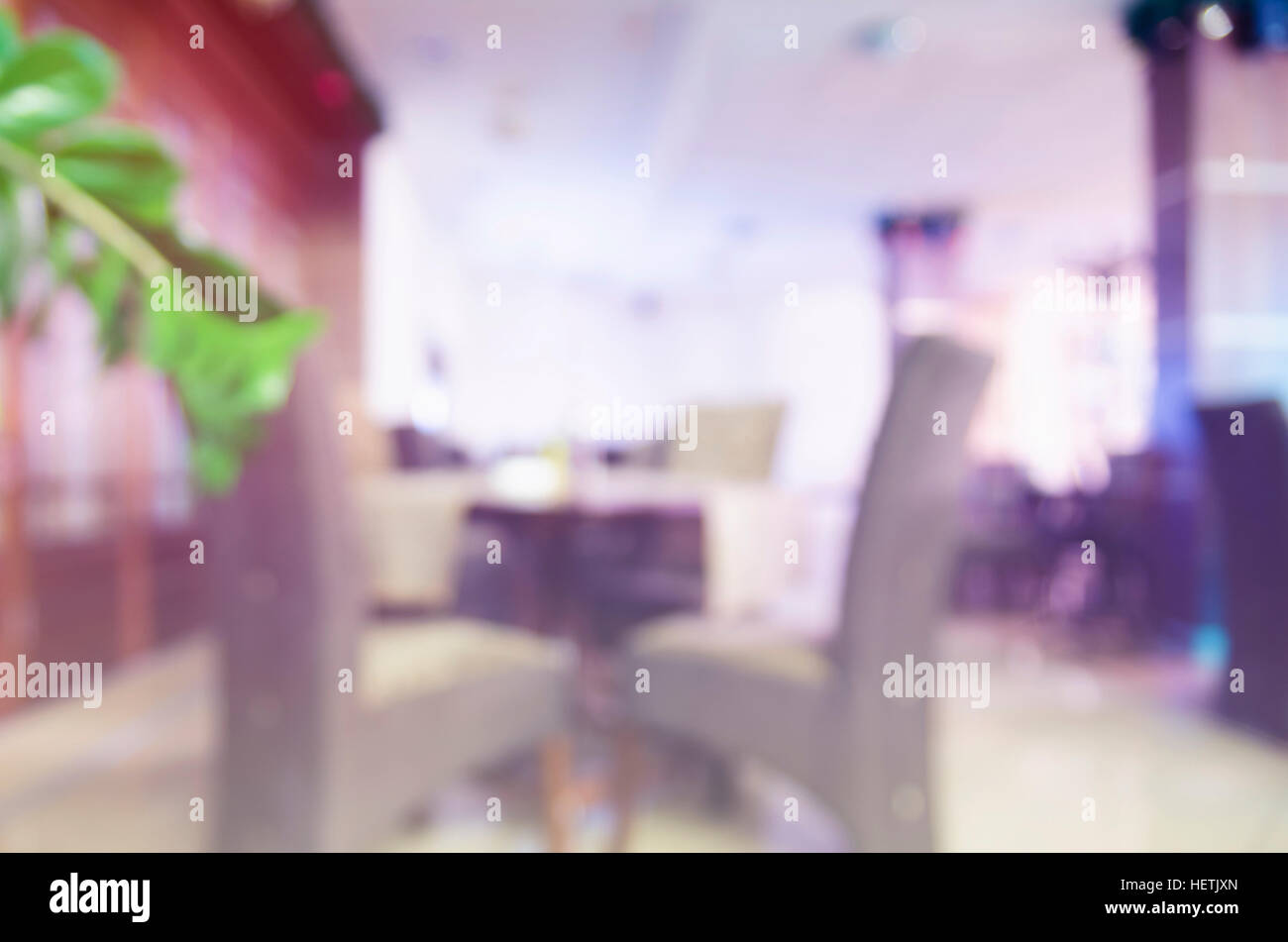 Unfocused image of empty restaurant seats with colorful lighting. - Stock Image