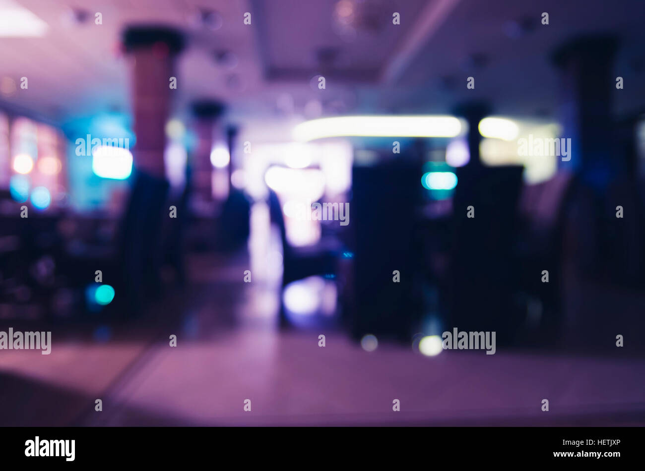 Unfocused image of empty restaurant interior with colorful lighting. - Stock Image