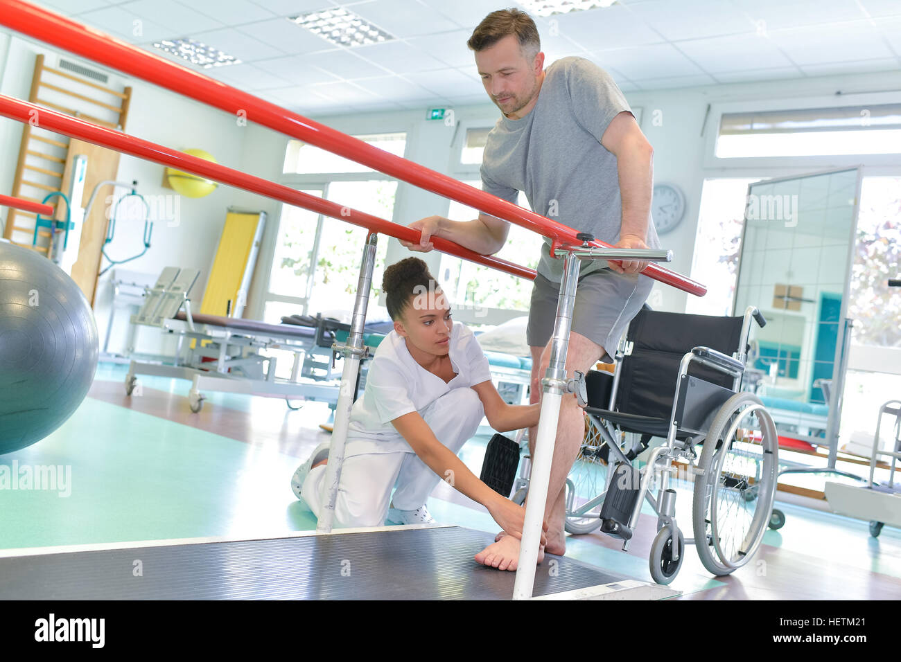 Occupational therapist helping patient to walk - Stock Image
