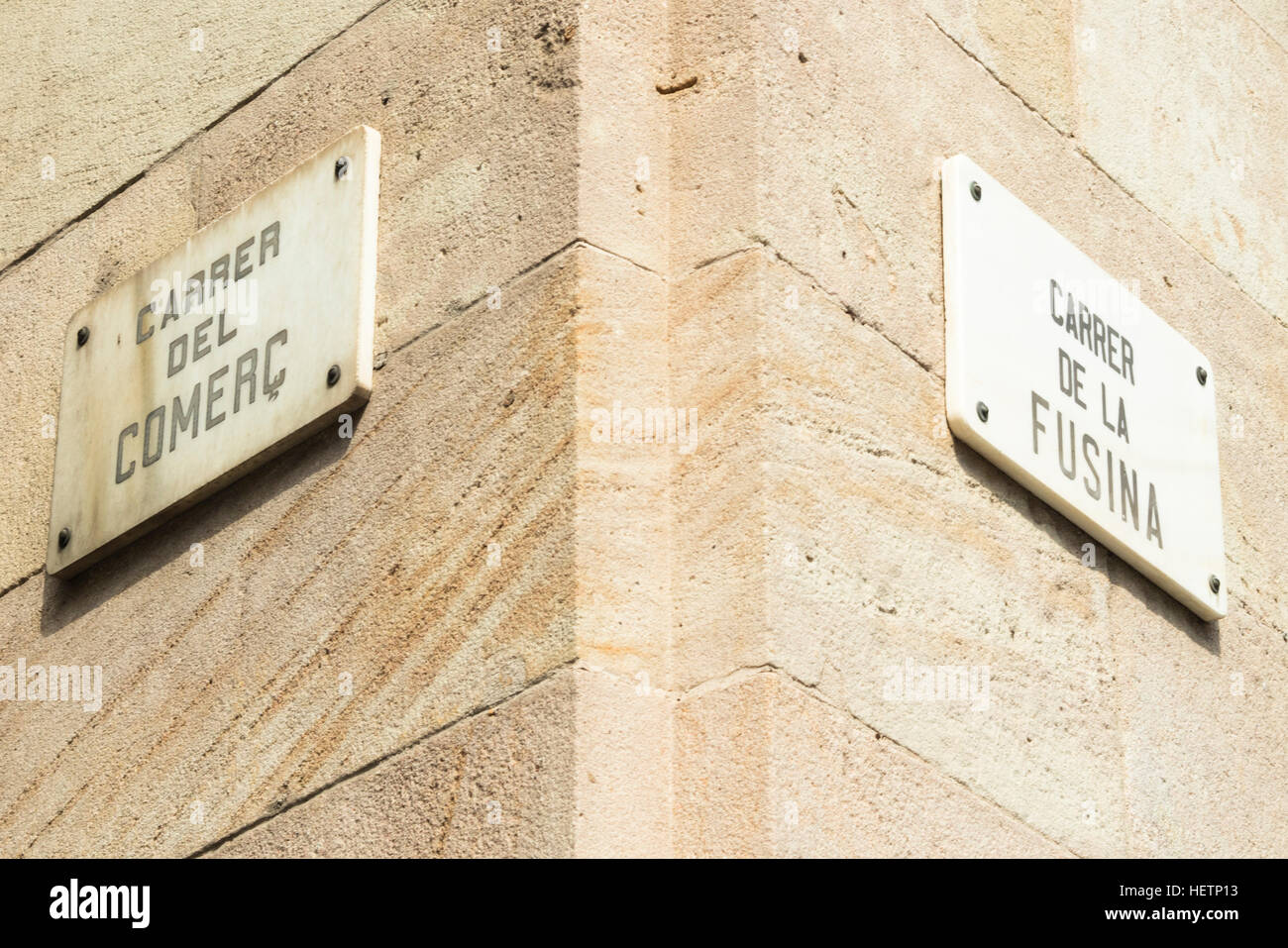 Detail of street signs with name of comerc street and fusina street on a stone facade of a building in Born, Barcelona, Stock Photo