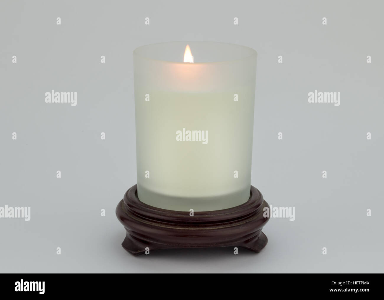 Single lit candle in glass on wood stand isolated on white
