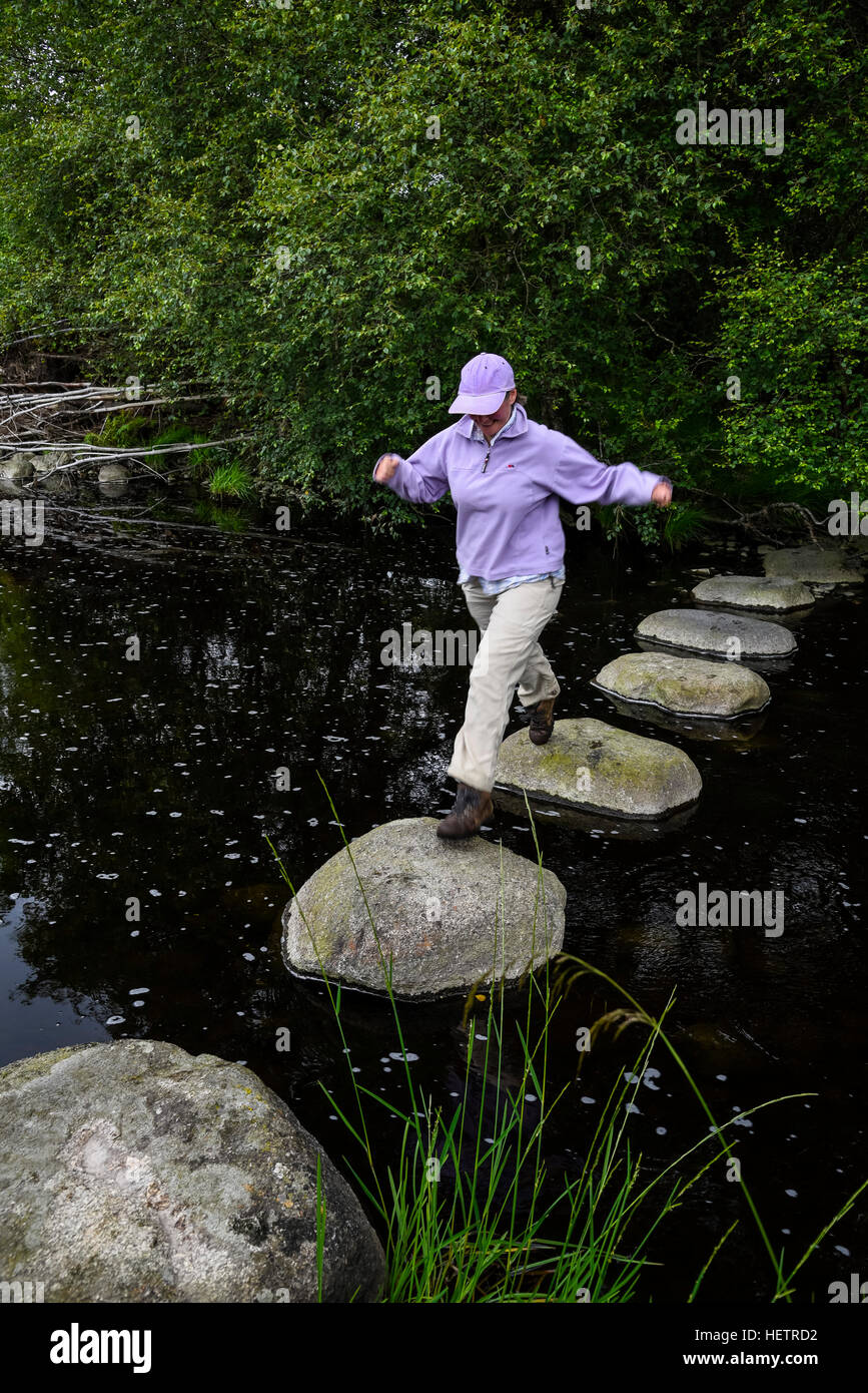 Woman crossing stepping stones across the River Dee, Dumfries & Galloway, Scotland - Stock Image