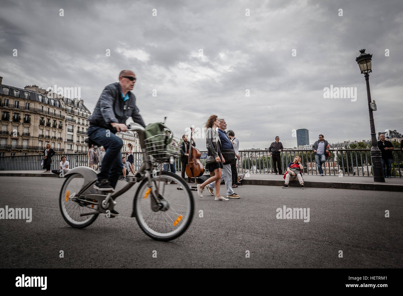 Man on a bike in the streets of Paris - Stock Image