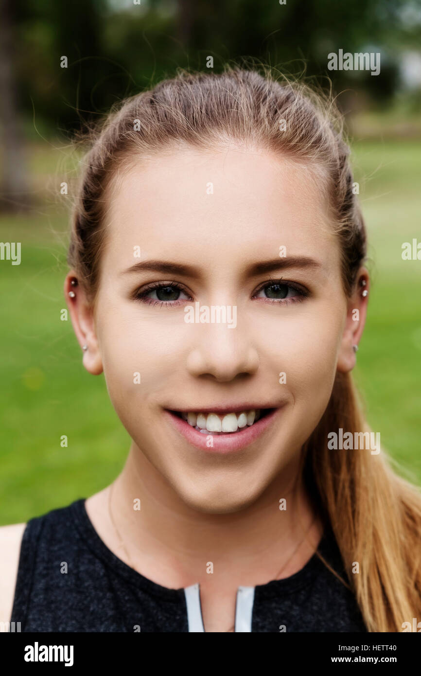 Blond Caucasian Woman Outdoors Smiling Portrait With Green Grass Background Stock Photo