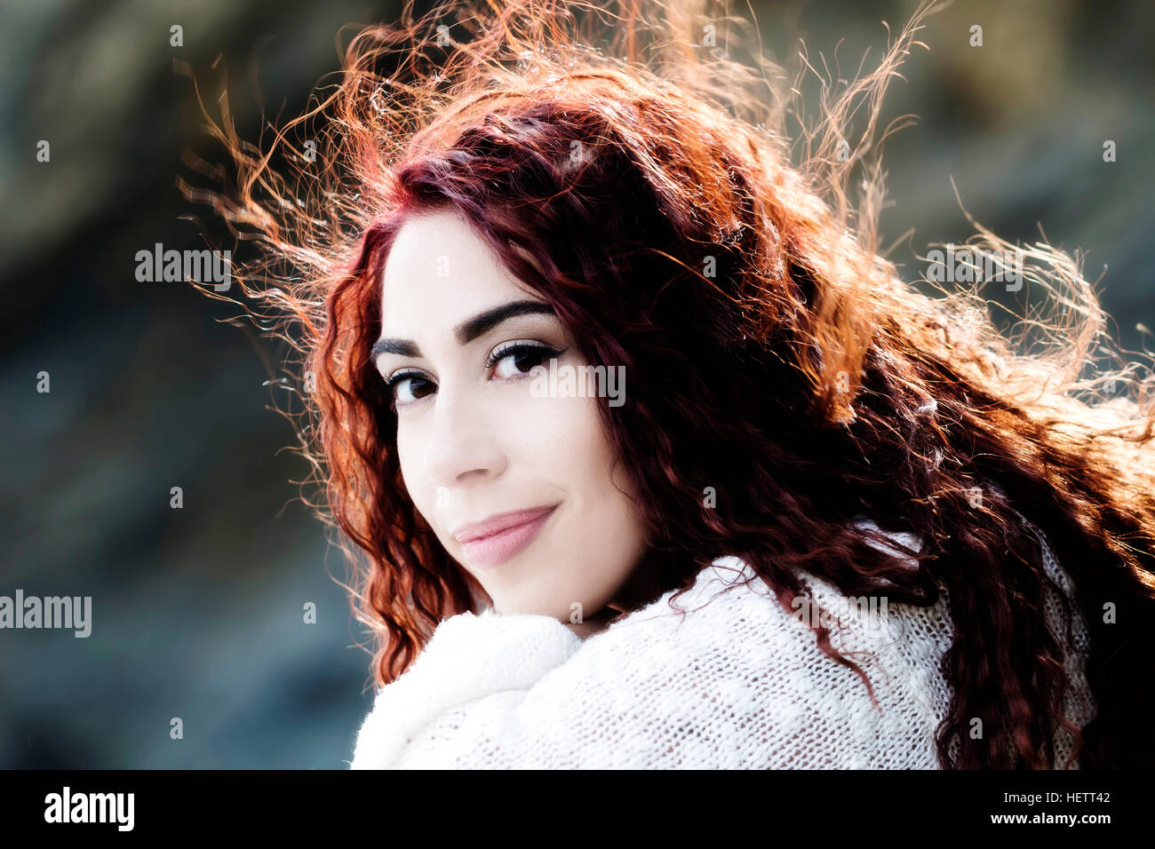 Hispanic Woman Outdoors Portrait White Knit Top And Hair Blowing In Wind Stock Photo