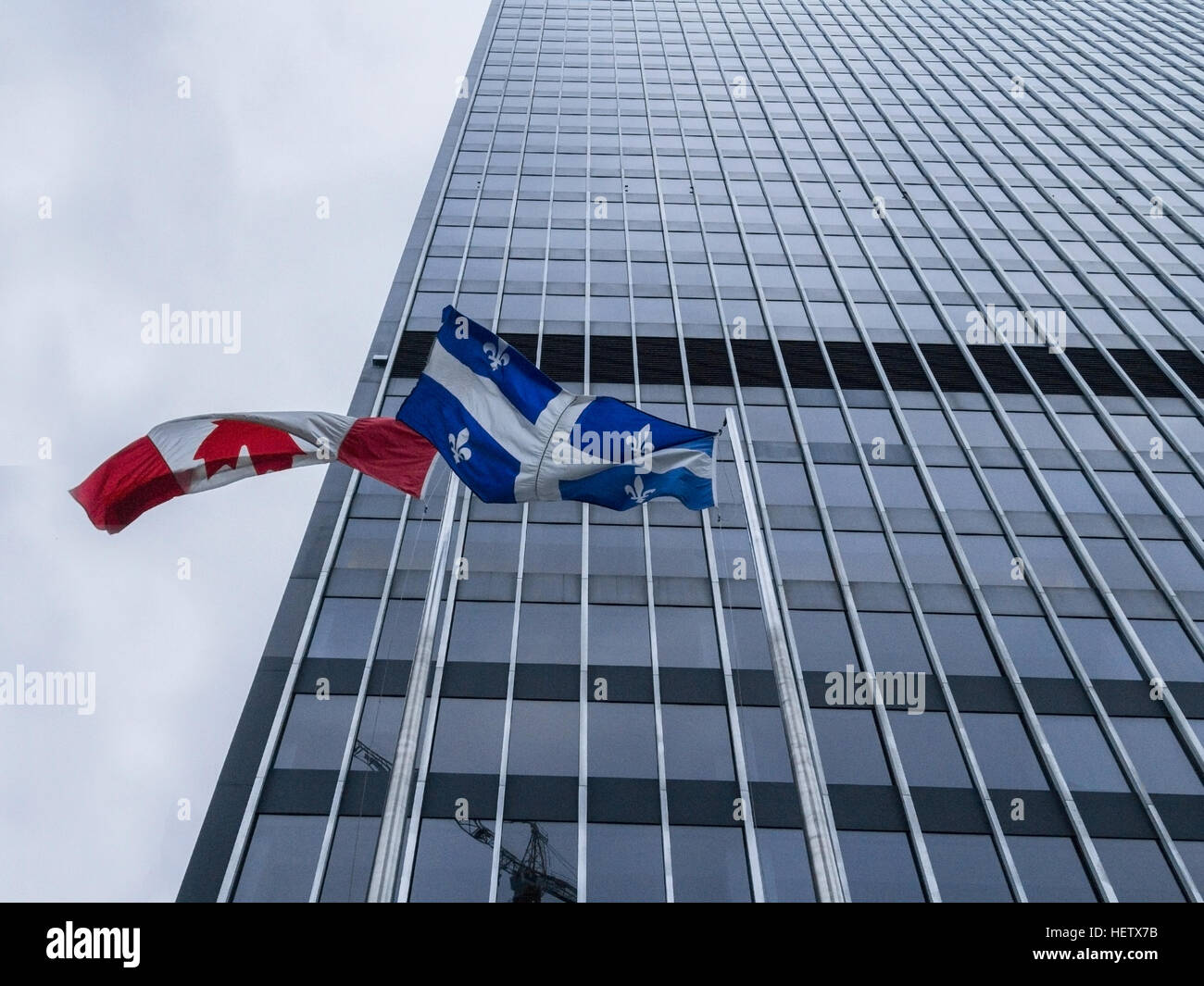 Canadian and Quebec flags in front of a skysrcaper - Stock Image