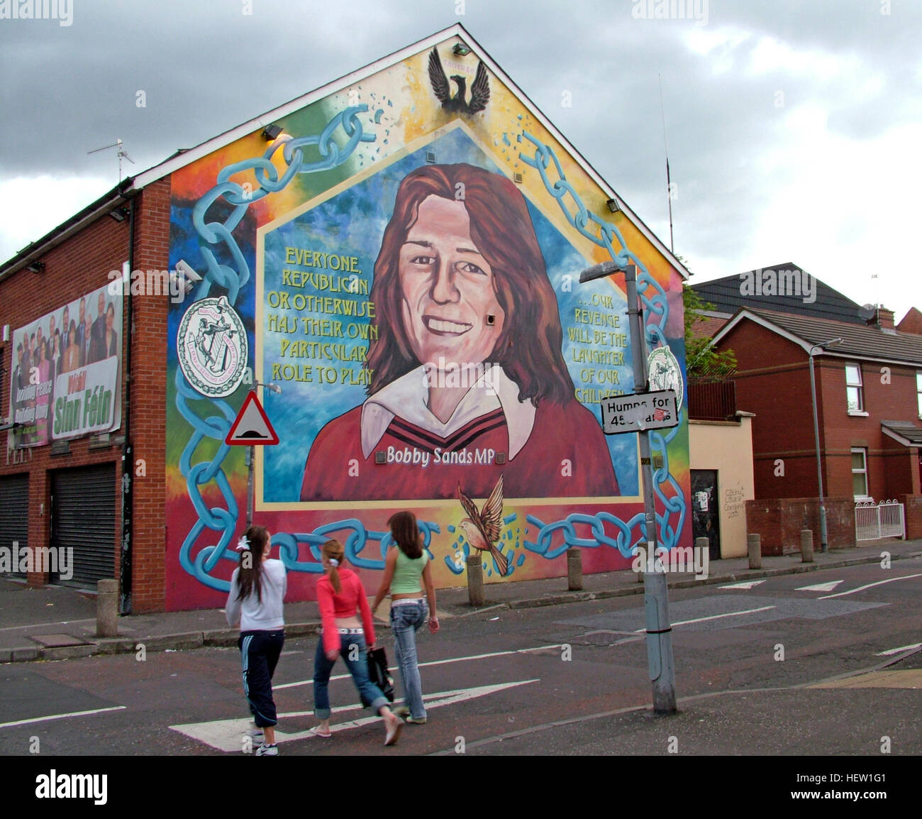 Belfast Falls Rd Republican Mural- Bobby Sands MP & Sinn Fein Office - with children crossing road - Stock Image