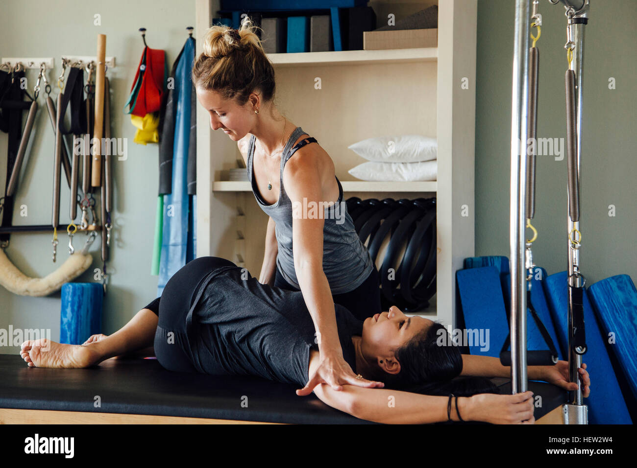 Woman and personal trainer using pilates reformer - Stock Image