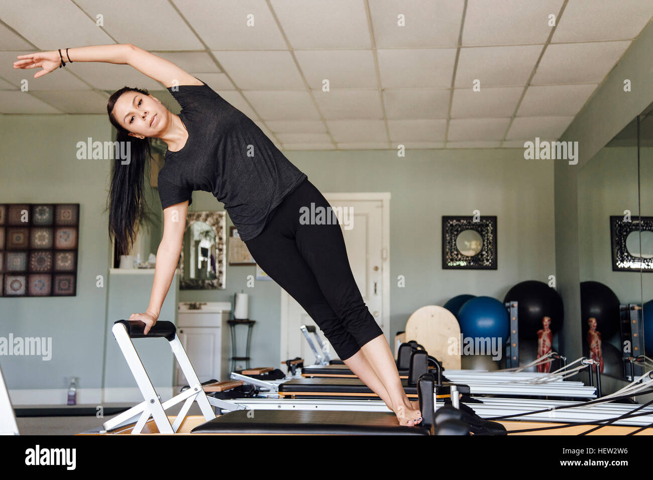 Woman in gym using pilates reformer - Stock Image