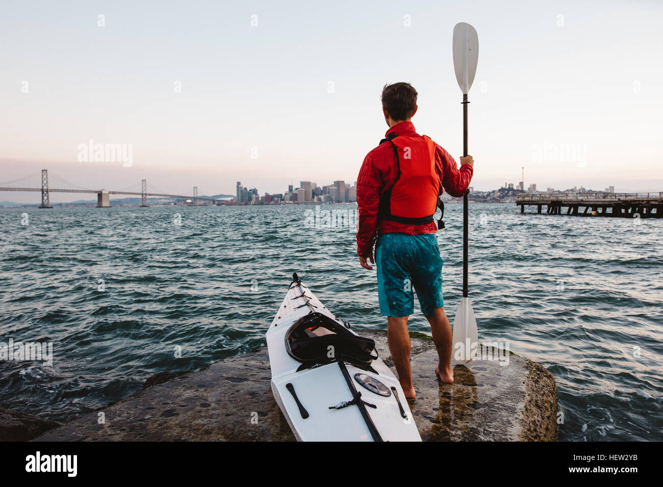 Man with kayak and oar, looking out to sea, San Francisco, California, USA - Stock Image