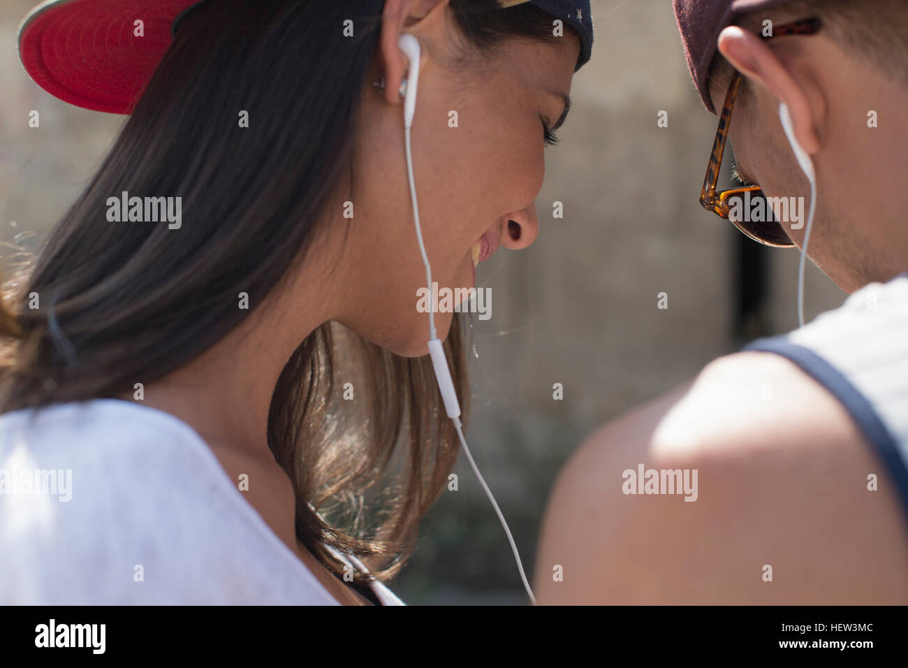 Couple wearing and sharing earphones - Stock Image