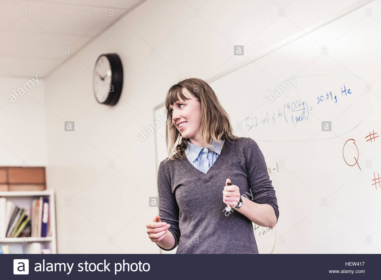Female teacher in front of whiteboard in high school lesson - Stock Image