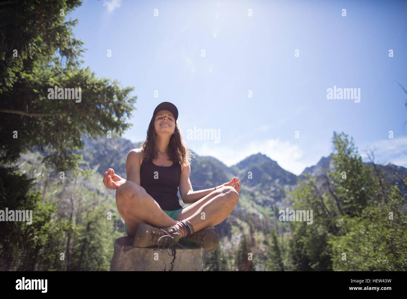 Hiker practising yoga on tree stump, Enchantments, Alpine Lakes Wilderness, Washington, USA - Stock Image