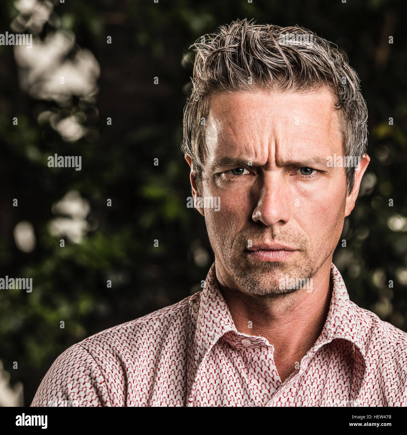 Portrait of man looking at camera scowling - Stock Image