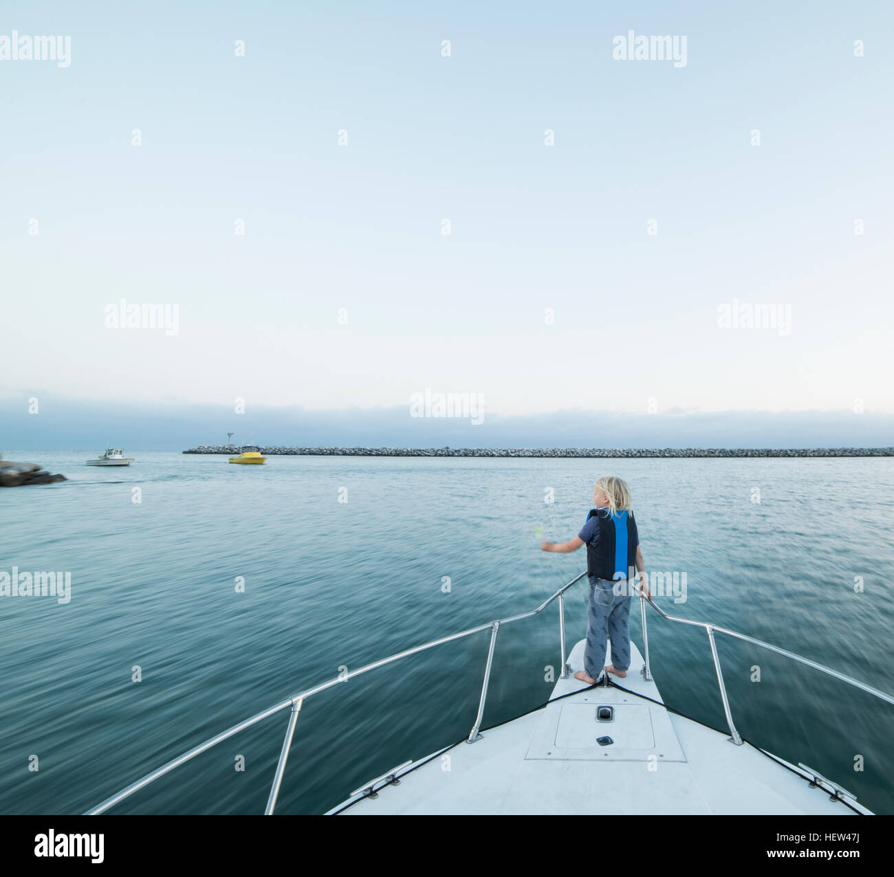 Rear view of boy on bow of boat, Dana Point, California, USA - Stock Image