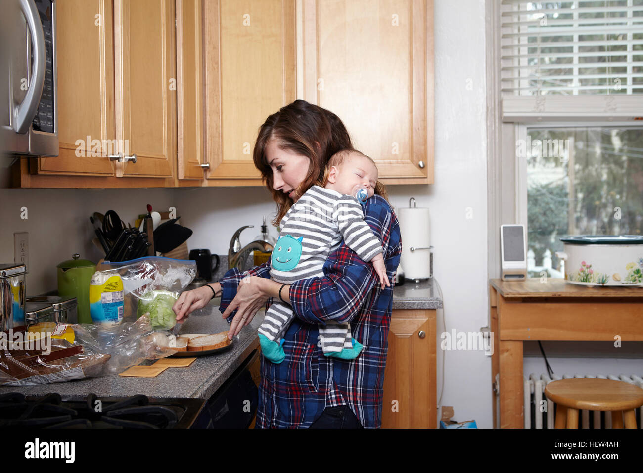 Mother holding sleeping baby boy and preparing sandwich - Stock Image