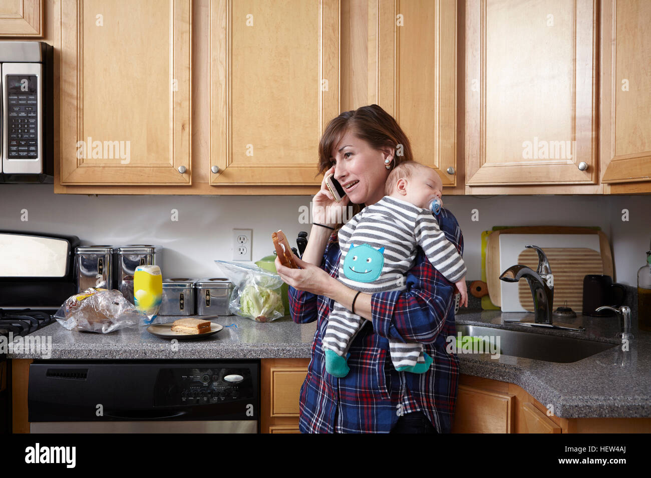Mother holding sleeping baby boy and making telephone call - Stock Image