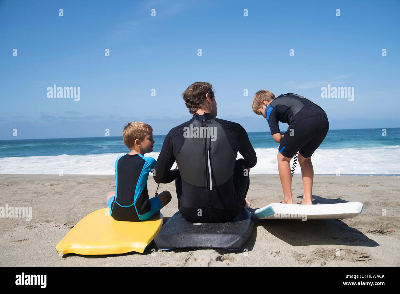 Rear view of father and two sons practicing with bodyboards on beach, Laguna Beach, California, USA Stock Photo